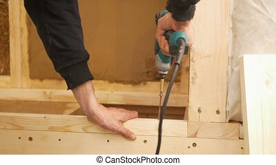 Male hand working with steel drill and screwdriver on wooden...