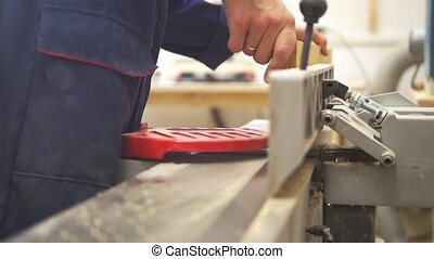 Male hand working with wooden plank using industrial...