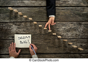 Male hand writing an encouraging message Dream big in a notepad as a businessman walks his fingers up wooden staircase