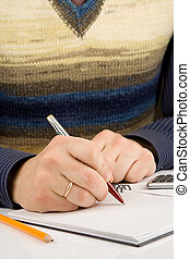 male hand writing by pen on notebook