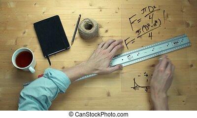 Male hand writing maths formulas math symbols at plastic glass with black marker