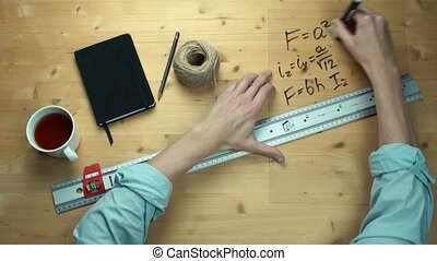 Male hand writing maths formulas math symbols at plastic glass with black marker