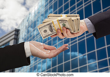 Male Hand Handing Stack of Cash to Woman with Corporate Building.