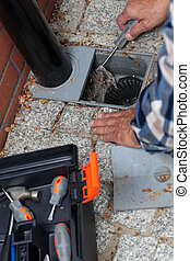 Male hands cleaning pavement drain hole - Close-up of a male...