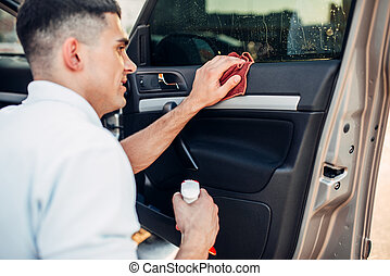 Male hands cleans auto on carwash station. Man rubbing...