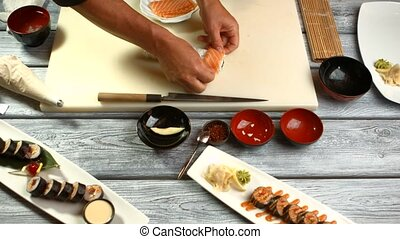 Male hands cook sushi.