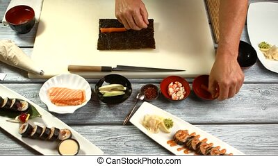 Male hands cooking sushi.