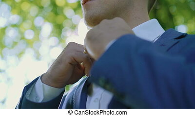 Male hands correct wedding bowtie on white shirt in the green light forest 4K