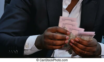 Male hands counting dollar bills on wooden table