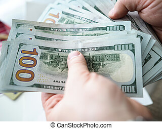 Male hands counting US hundred bucks bills