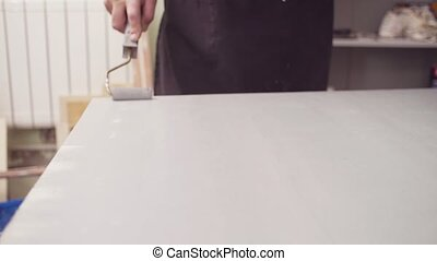 Male hands covering a wooden surface with a primer - Crane ...