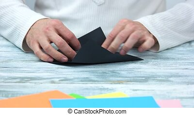 Male hands creating origami figure. Black paper for origami,...