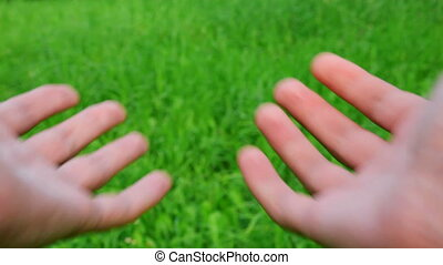 male hands cupped on green grass background