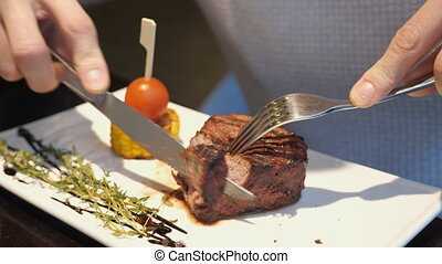 male hands cuts meat. - male hands cuts meat, close up