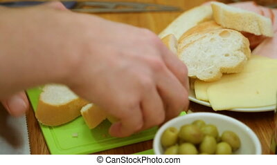 Male hands cutting baguette on board