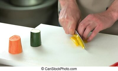 Male hands cutting bell pepper.
