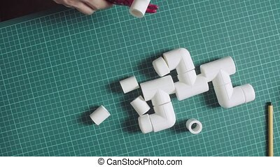 Male hands cutting polypropylene pipe - Crane shot. Close up...