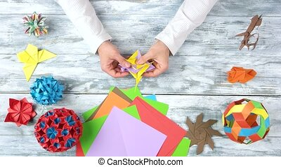 Male hands folding origami toy. Paper folding art. Origami...