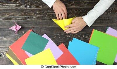 Male hands folding yellow paper sheet. Pink orizuru paper...