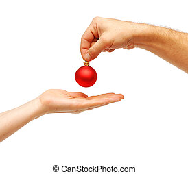 male hands give a christmas ball to female hands. All over...
