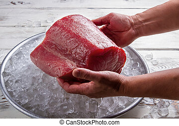 Male hands hold fish meat.