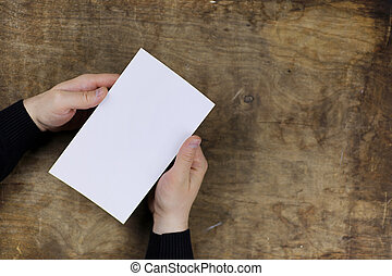 male hands holding a white blank sheet of paper