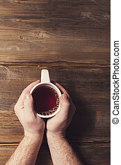 Male hands holding a white Cup with tea on a background of old wooden planks
