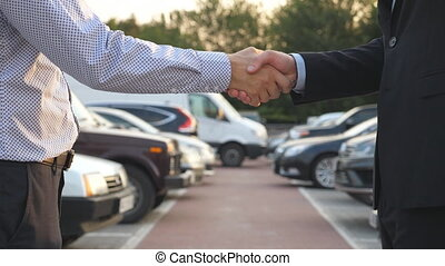 Male hands in suit giving keys of car to his friend. Arm of...