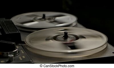 Male hands include rewind on vintage professional analog reel to reel tape recorder. Transparent rotating coils on black studio background. Retro tape. Close up. Slow motion