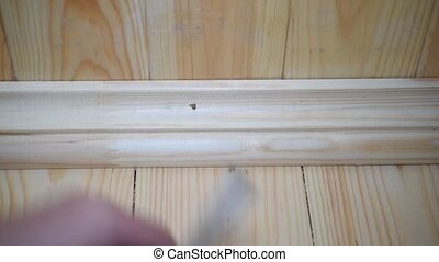 Male hands installing a wooden skirting board by nailing it...