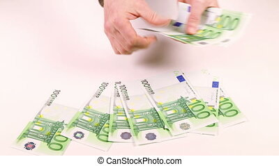 Male hands lay out money in denominations of 100 Euros on...