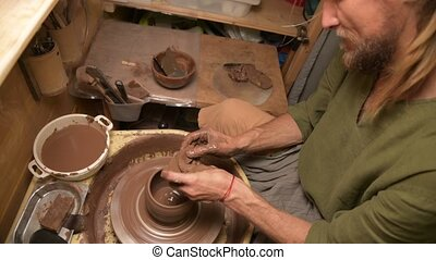 Male hands making a clay bowl on a potter's wheel. ...
