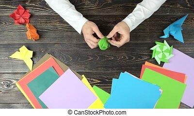 Male hands making origami boat. Man folding origami figure...