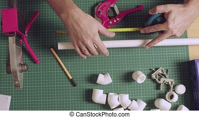 Male hands measuring and cutting polypropylene pipe - Top ...