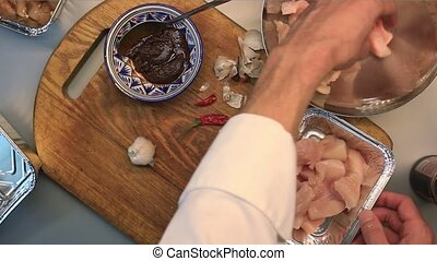 Male hands mixing chicken with pepper and garlic