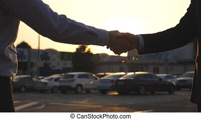 Male hands of dealer giving keys of car to client with sun...