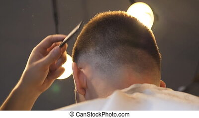 Male hands of hairstylist combing and cutting hair of...