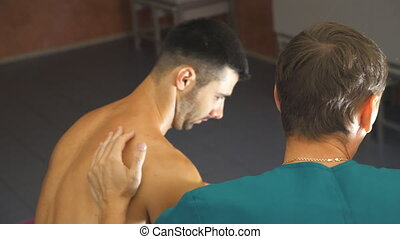 Male hands of professional massagist doing healing rubdown...