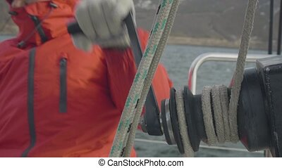 Male hands of sailor man reel up ropes on board sailing...