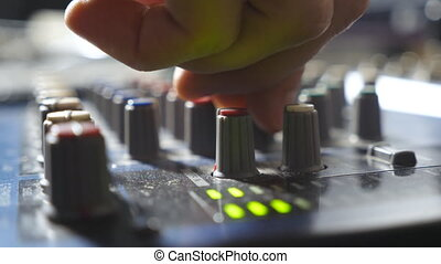 Male hands of sound engineer adjusting the knobs on mixer...