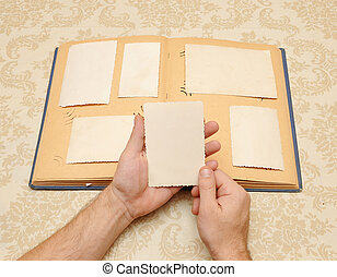 male hands on an old vintage photo album