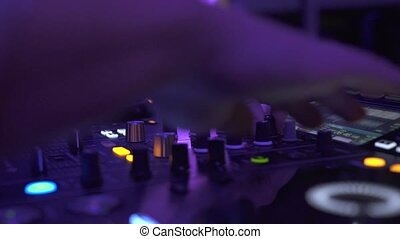 Male hands on dj sound console mixing house music at night...