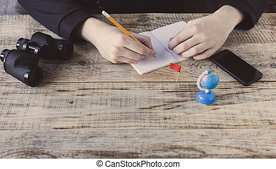 Male hands over cafe background - table wooden plancs, smartphone, nootbook, pencil, Globe, binoculars, flag, aim, achieving, target, tourism, travel. Tourism. Hipster style. Top view with copy space. Free space for text.