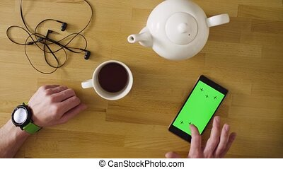 Male hands paying a card in the smartphone - Top view. Green...