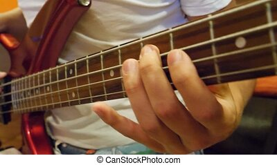 Male hands playing bass guitar