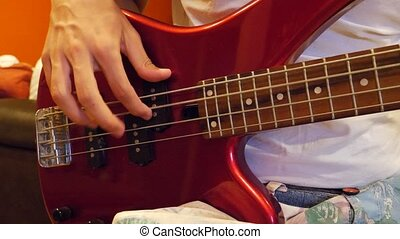 Male hands playing bass guitar at home or in recording...
