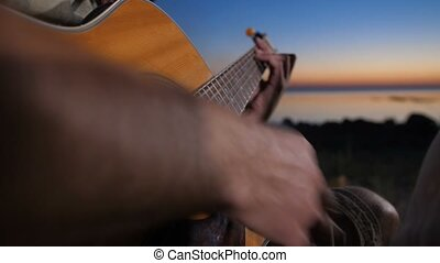Male hands playing guitar near campfire at night - Closeup...
