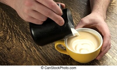 Male hands pouring latte art. Cup with drink, wooden...