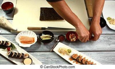 Male hands preparing sushi.