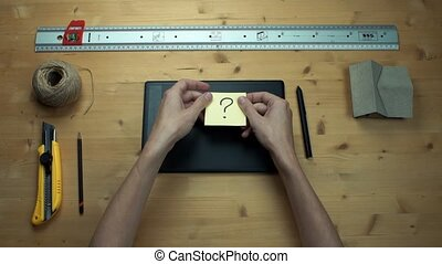 Male hands putting off sticky note with question sign using graphic tablet.